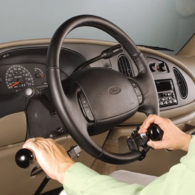 Driver's side of car pictured with driver using hand controls and a steering knob to drive