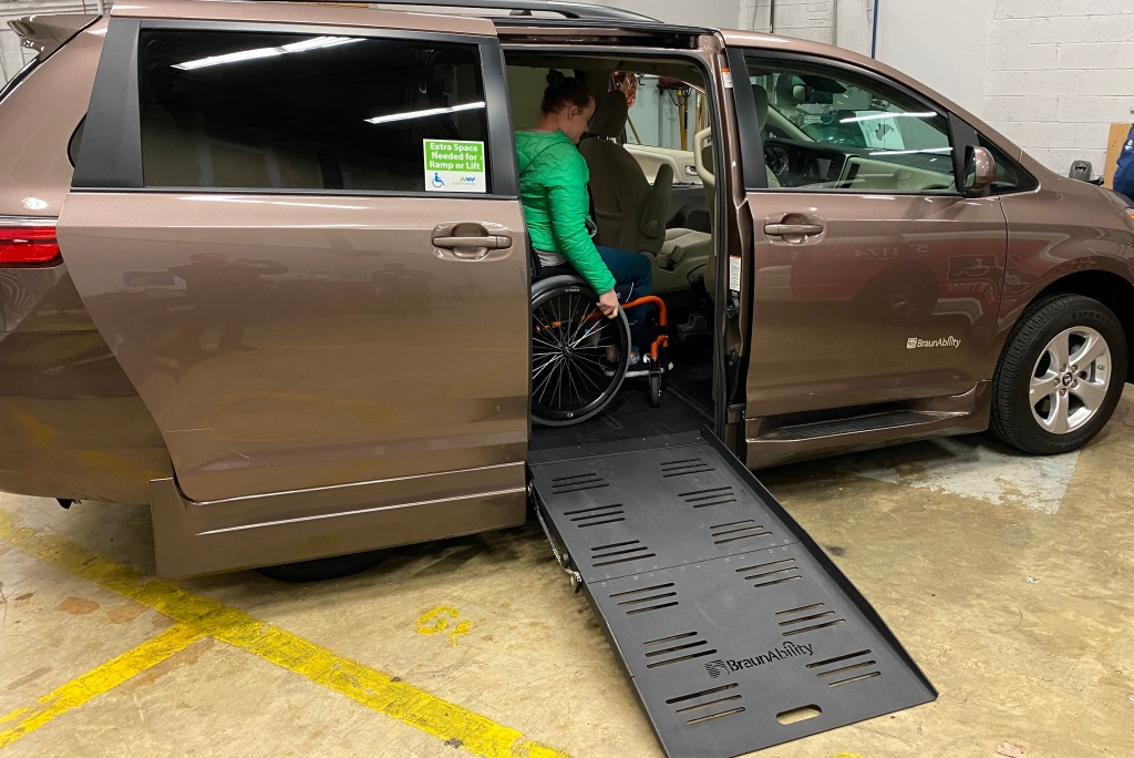 Wheelchair accessible van with ramp extended out, manual wheelchair user inside vehicle