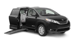 Black toyota sienna with ramp extending from passenger sliding door